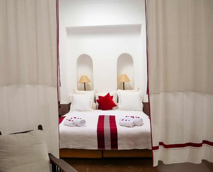 Photo d'un lit blanc et rouge dans un riad à Marrakech