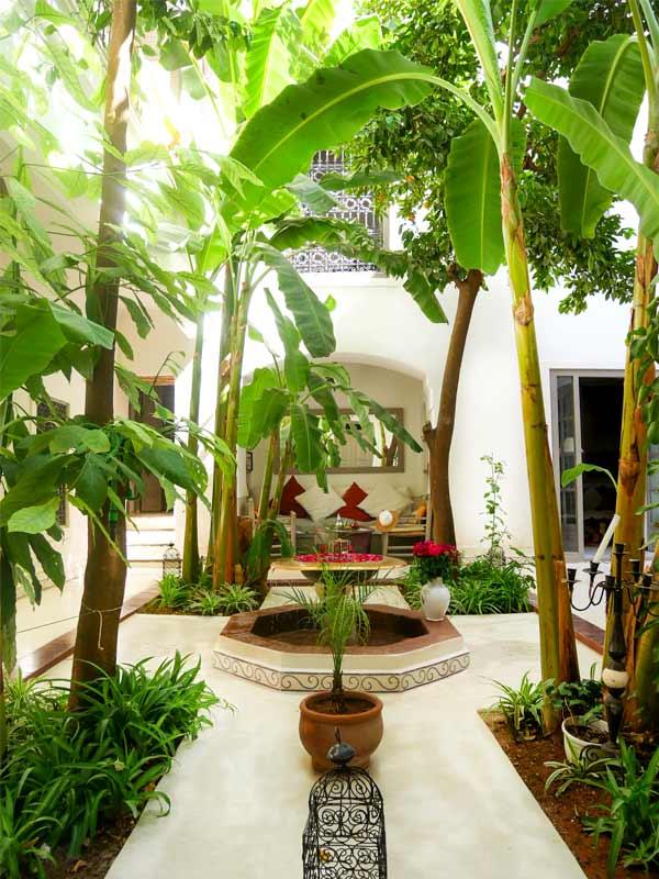 Photo d'un patio avec une fontaine, des orangers et bananiers dans un riad à Marrakech au Maroc
